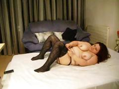 Fat brunette wearing black stockings sticks dildo in her fat pussy